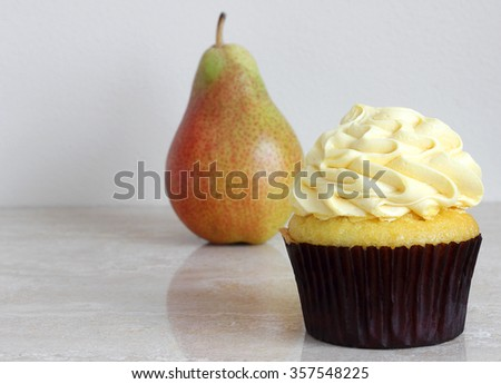 Healthy eating concept.  Will it be a luscious lemon cupcake or fresh, juicy low calorie pear? - stock photo