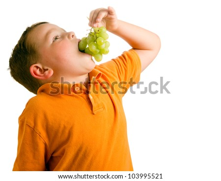 Healthy eating concept with child eating grapes isolated on white - stock photo