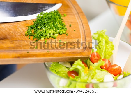 healthy eating, cooking, vegetarian food and dieting concept - close up of chopped onion on wooden cutting board and vegetable salad in bowl