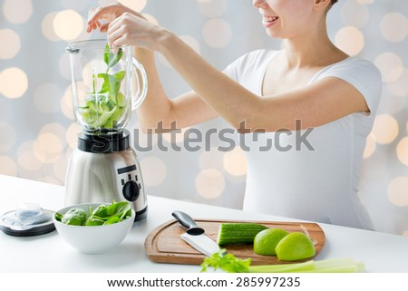 healthy eating, cooking, vegetarian food, dieting and people concept - close up of young woman with blender and green vegetables making detox shake or smoothie over holidays lights background - stock photo