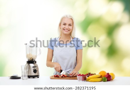 healthy eating, cooking, vegetarian food, dieting and people concept - smiling young woman with blender chopping fruits and berries for fruit shake over green natural background - stock photo