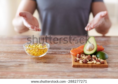healthy eating, diet and people concept - close up of male hands showing food rich in protein on cutting board on table - stock photo