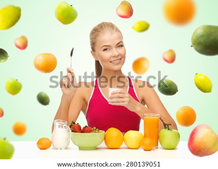 healthy eating, diet, organic food and people concept - happy woman eating yogurt and having breakfast over green background with falling fruits - stock photo