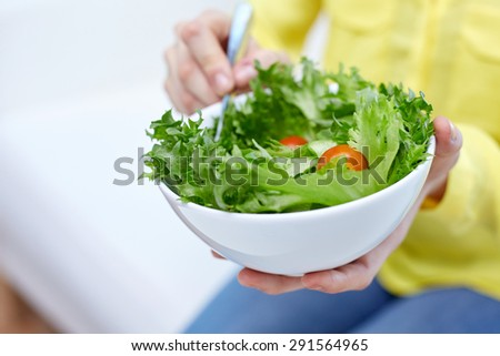 healthy eating, dieting and people concept - close up of young woman eating vegetable salad at home - stock photo