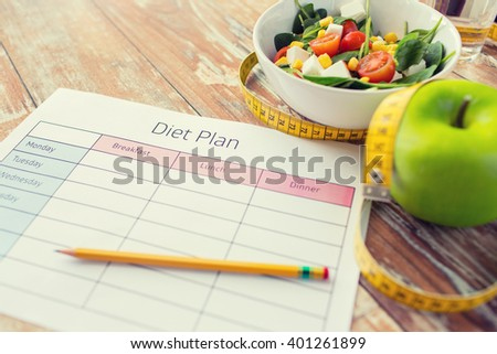 healthy eating, dieting, slimming and weigh loss concept - close up of diet plan paper green apple, measuring tape and salad - stock photo