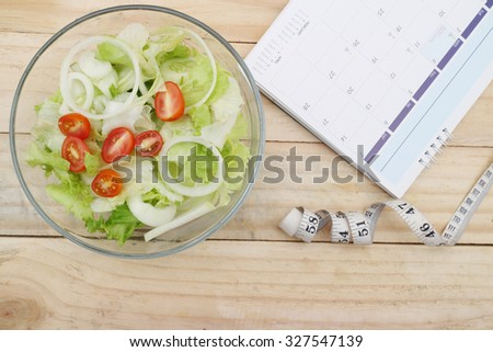 healthy eating, dieting, slimming and weigh loss concept - close up of salad, measuring tape  - stock photo