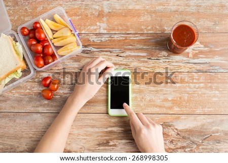 healthy eating, dieting, technology and people concept - close up of woman hands with blank smartphone and food in plastic container on table at home - stock photo