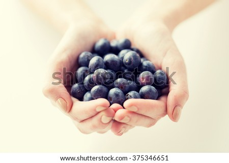 healthy eating, dieting, vegetarian food and people concept - close up of woman hands holding blueberries at home - stock photo