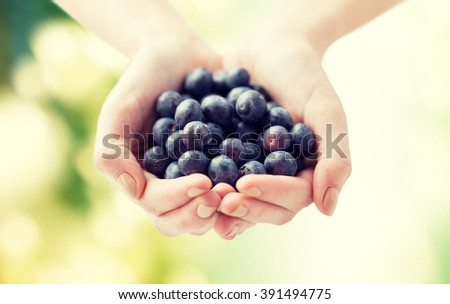 healthy eating, dieting, vegetarian food and people concept - close up of woman hands holding blueberries over green natural background - stock photo