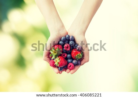 healthy eating, dieting, vegetarian food and people concept - close up of woman hands holding different ripe summer berries over green natural background - stock photo