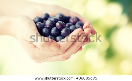 healthy eating, dieting, vegetarian food and people concept - close up of woman hands holding ripe blueberries over green natural background - stock photo