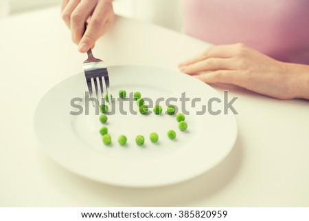 healthy eating, dieting, vegetarian food and people concept - close up of woman with fork eating peas in shape of heart - stock photo