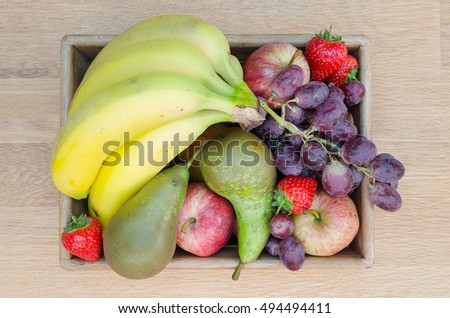 healthy eating, dieting, vegetarian food concept - five a day. Fruits and berries in a wooden basket / crate on table.