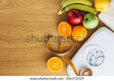 Healthy eating, fitness and weight loss concept, white scale with fruit on a wooden table, blank copy space at left - stock photo