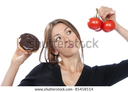 Healthy eating food concept. Woman comparing unhealthy donut and organic red tomatoes, thinking isolated on a white background - stock photo