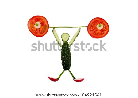 Healthy eating. Funny little man of the cucumber slices raises tomato bar. - stock photo