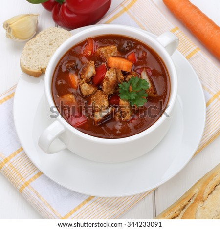 Healthy eating goulash soup meal with baguette, meat and paprika in cup