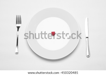 Healthy eating in the restaurant and diet Topic: white plate with a ripe raspberry and a metal knife and fork lying on a white table in the studio isolated top view