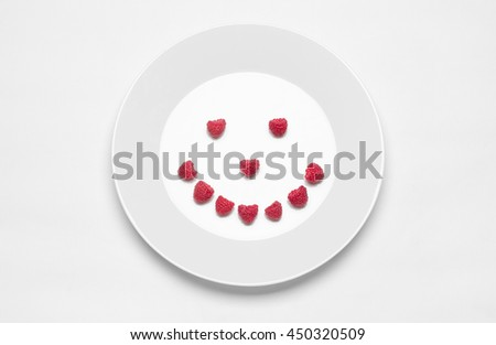 Healthy eating in the restaurant and diet Topic: white plate with raspberries lying on a white table in the studio isolated top view berry smile