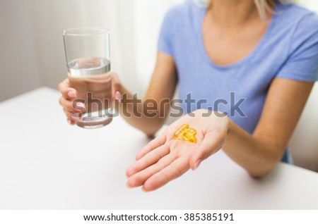 healthy eating, medicine, health care, food supplements and people concept - close up of woman hands holding pills or fish oil capsules and water glass at home - stock photo