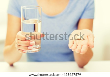 healthy eating, medicine, health care, food supplements and people concept - close up of woman hands holding pills and water glass at home - stock photo