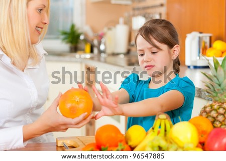 Healthy eating - mother and child sitting in the kitchen with different kinds of fruits, the kid doesnt like fruits for breakfast food - stock photo
