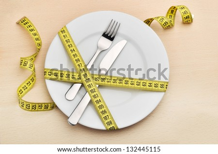 Healthy eating or dieting concept. Empty plate, fork and knife wrapped in measuring tape. - stock photo