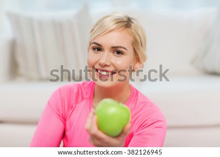healthy eating, organic food, diet and people concept - happy woman eating green apple at home - stock photo