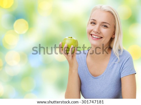 healthy eating, organic food, fruits, diet and people concept - happy woman eating green apple over summer green holidays lights background - stock photo