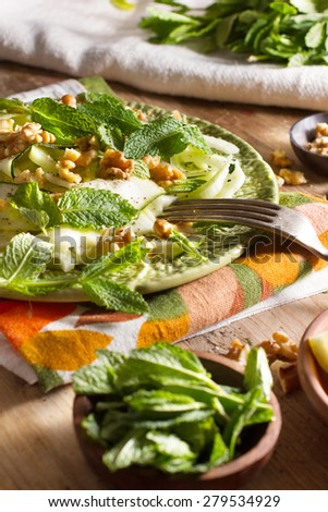 Healthy eating: raw fennel salad with walnuts, raw courgettes, mint leaves and lemon juice. Zesty, fresh, summery and light food. Perfect for a diet. - stock photo