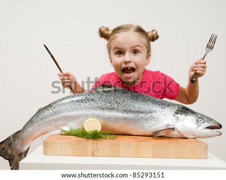 Healthy eating seafood - little girl and big  fish - stock photo