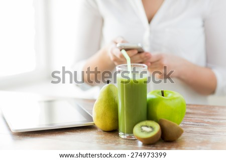 healthy eating, technology, diet and people concept - close up of woman hands holding smartphone with tablet pc, fruits and fresh juice sitting at table - stock photo