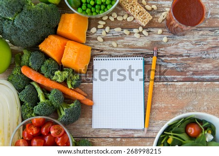 healthy eating, vegetarian food, advertisement and culinary concept - close up of ripe vegetables and notebook with pencil on wooden table - stock photo