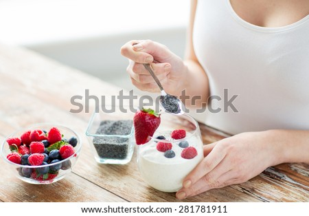 healthy eating, vegetarian food, diet and people concept - close up of woman hands with yogurt, berries and poppy or chia seeds on spoon - stock photo