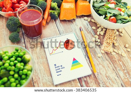 healthy eating, vegetarian food, diet and weight control concept - close up of ripe vegetables and notebook with charts and calories on wooden table - stock photo