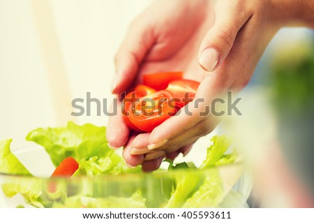 healthy eating, vegetarian food, dieting and people concept - close up of young woman cooking vegetable salad and adding tomatoes at home