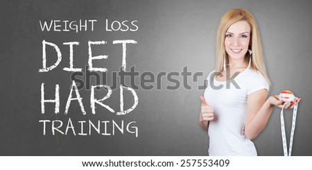 Healthy eating - Weight loss diet - Beautiful pretty young woman with fruit and measuring tape - isolated on old grey wall background with WEIGHT LOSS DIET HARD TRAINING text - stock photo