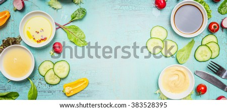 Healthy Eating with vegetables salad ingredients, dressing  and cutlery on turquoise blue shabby chic background, top view, banner. Healthy lifestyle or diet food concept - stock photo