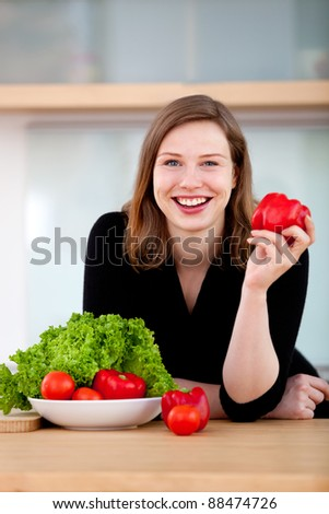 Healthy eating woman preparing a vegetable salad and smiling - stock photo