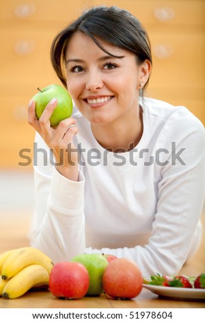 Healthy eating woman smiling and holding an apple on her hand - stock photo