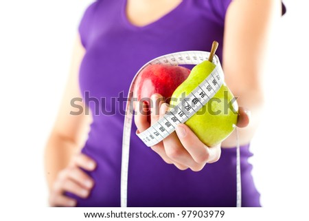 Healthy eating - woman with apple and pear and measuring tape - stock photo
