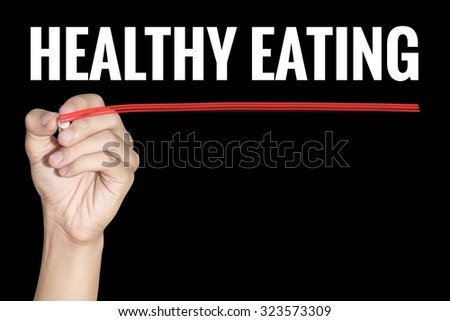 Healthy Eating word writting by men hand holding highlighter pen with line on black background - stock photo