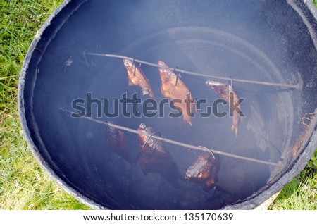healthy ecological fish smoke in smokehouse made of old rusty barrel. - stock photo