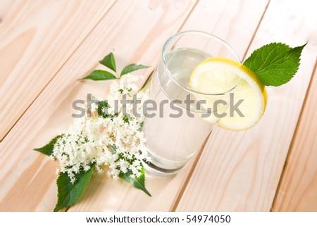 Healthy elder flower juice with lemon on wooden background. - stock photo