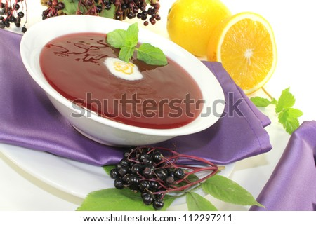 healthy elderberry soup with blobs of cream and mint on a bright background