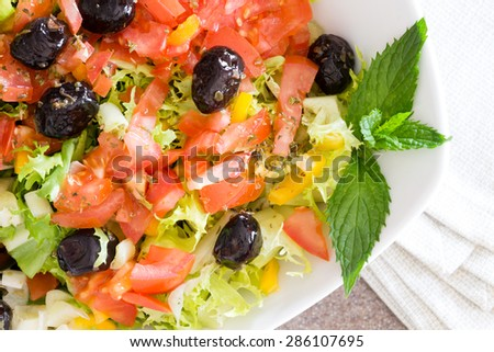 Healthy farm fresh Mediterranean salad with black olives, lettuce, tomato and sweet bell peppers garnished with sprigs of mint for flavoring, close up detail