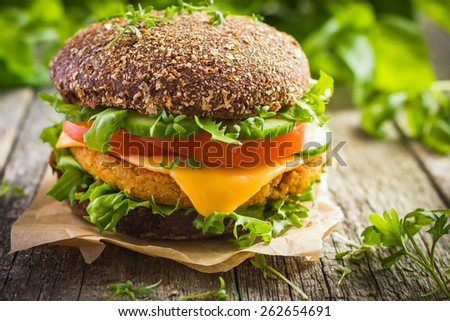 Healthy fast food. Rye burger with fresh vegetables, chickpeas patty and cheese on old wooden  background - stock photo