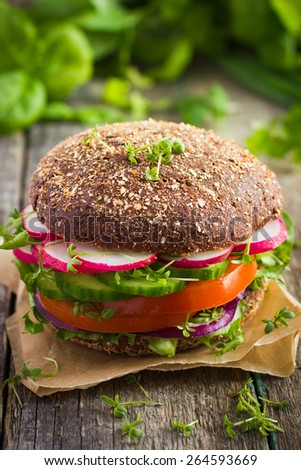 Healthy fast food. Vegan rye burger with fresh vegetables on old wooden  background - stock photo