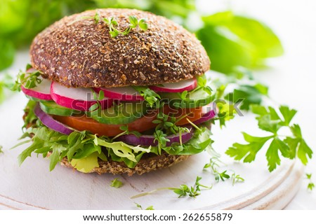 Healthy fast food. Vegan rye burger with fresh vegetables on white wooden  background - stock photo