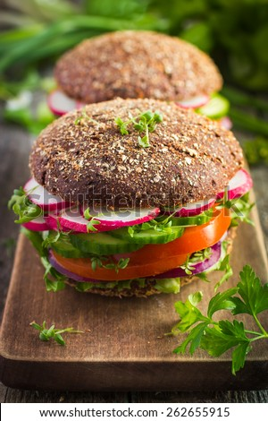 Healthy fast food. Vegan rye burger with fresh vegetables on  wooden  background - stock photo